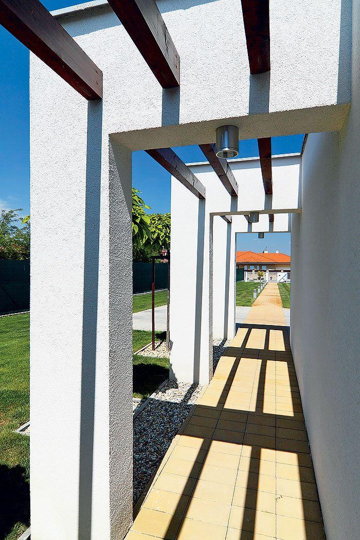 """K prízemnému domu na úzkom pozemku mala, navyše, patriť aj dvojgaráž. Architekti sa rozhodli vyčleniť ju z hmoty domu: """"Zároveň sme tu urobili nástup so stĺporadím, nasvietili ho, pridali sme pergolu... Bol to skôr výtvarný zámer, než čisto funkčná záležitosť,"""" objasňujú autori. Chodník lemovaný stĺpmi a geometricky strihanými stromčekmi však funguje spoľahlivo – bez zaváhania vás privedie k vstupu do domu."""
