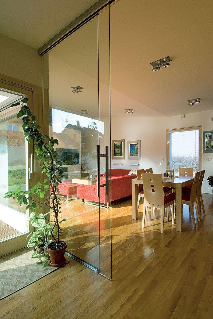 O tom, že domáci obľubujú otvorený interiér, jasne vypovedá obývačka plynule prechádzajúca do jedálne a kuchyne a vizuálny kontakt so vstupnou halou aj exteriérovým obytným priestorom v átriu. Zámer architektov a predstavy majiteľov ešte umocňujú posuvné sklenené dvere.