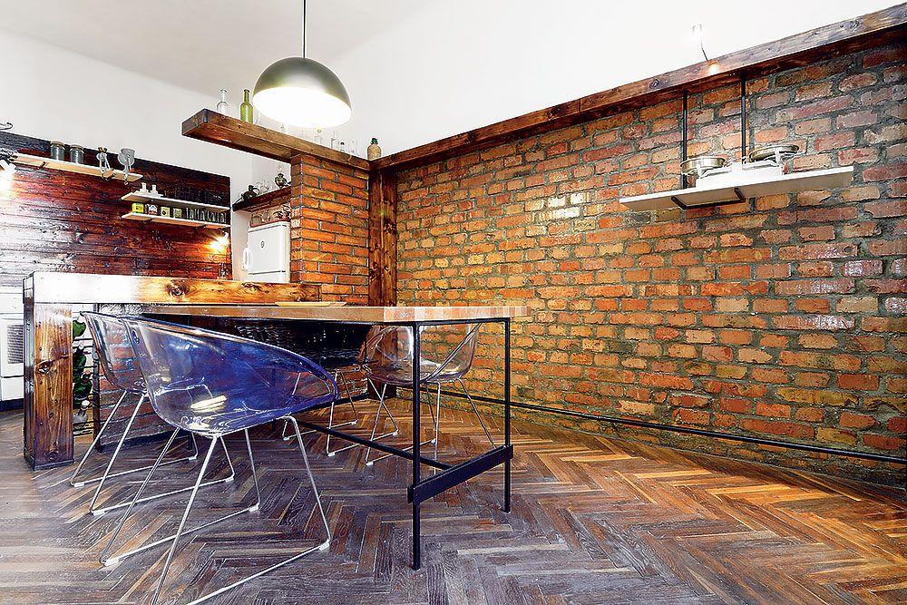 """Tehlová stena je nielen praktická (tehly sú napustené umývateľným lakom, aby bola exponovaná plocha pri jedálenskom stole odolná a dala sa umyť). """"Bol tu aj emotívny moment,"""" približuje svoj zámer Viliam Krížik. """"Toto je typický starý tehlový obytný dom, preto som chcel odkryť vrstvu tehly, ktorá je krásna a pre tieto stavby príznačná. Považujem za dôležité určité vtiahnutie hodnôt, ktoré poskytuje exteriér alebo konštrukcia objektu, aj do interiéru, čím sa vytvorí istá previazanosť. Často stačí len odkryť to pôvodné, čo byt v sebe nesie, a s minimom zariaďovacích prvkov vznikne funkčne a esteticky impozantný priestor s atmosférou, akú bývanie v moderných bytoch nemôže poskytnúť."""""""
