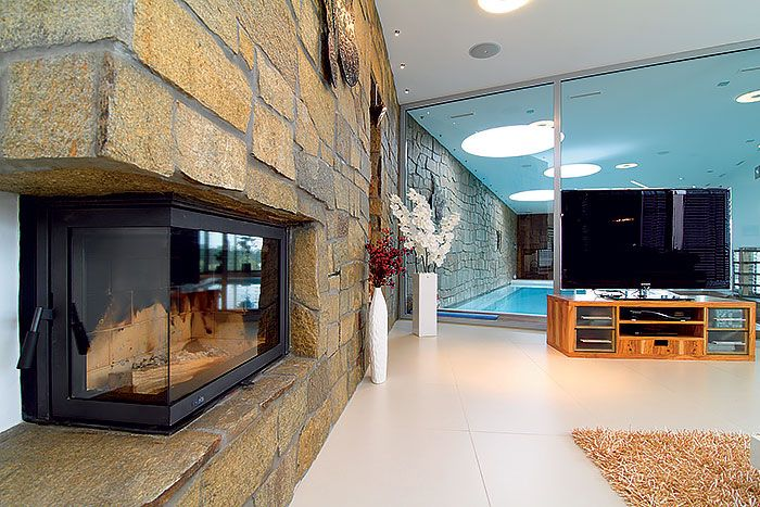 Štruktúra obkladu zo zlatej ruly zvýraznila ohyb severnej steny a opticky prepojila priestor obývačky s wellness. Večer si na kameň posvietia bodovým osvetlením, ktoré na kamennom povrchu efektne zvýrazní prirodzenú nerovnosť.