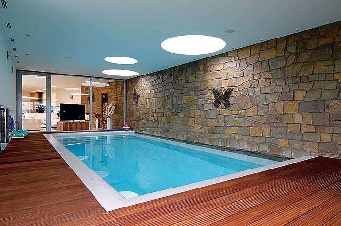 Vnútorný bazén a ani tvar domu nedáva predpoklad na stavbu pasívneho domu. Objekt sa však vďaka vykurovaniu pomocou tepelného čerpadla zem-voda a použitými stavebnými materiálmi blíži parametrom nízkoenergetickej stavby. Pod drevenou podlahou s vekom 2 × 4 m je ukrytá strojovňa na protiprúd. Večer, keď si zažnú bodové osvetlenie, objavia sa efekty a odlesky na štruktúre kameňa. Obklad zo zlatej ruly ošetrili impregnáciou proti vlhkosti, kameň bez ujmy vydrží aj ponorený pod vodnou hladinou.