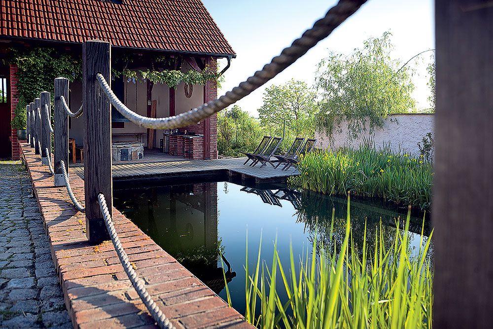 Medzi obytnými budovami sa na ľavej strane zrkadlí hladina veľkého kúpacieho jazierka hlbokého dva metre. Celoročne tu plávajú ryby a spolu s nimi v lete aj majitelia.