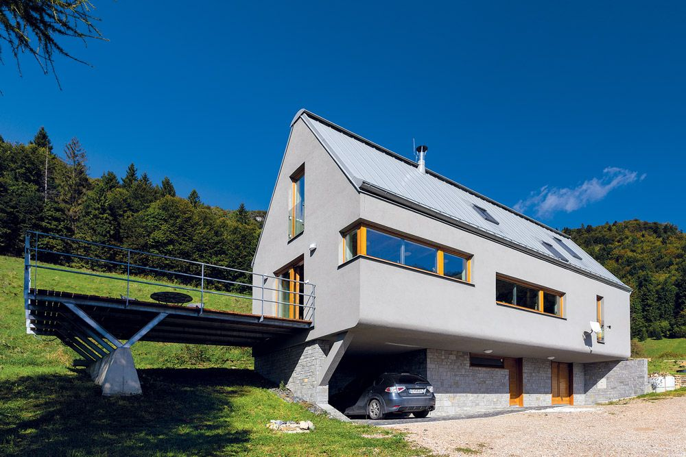 """Moderný prístup k tradičnej forme. Dom s tradičným predĺženým pôdorysom a sedlovou strechou je položený na ustupujúcom sokli, ktorý umožnil veľkorysejšie riešenie vstupu. Kompozične mierne graduje pri západnej štítovej stene, kde sa pripája """"levitujúca"""" terasa. Kompaktnú formu dopĺňa podobne celistvá farebnosť, ktorá využíva úzku farebnú škálu prevažne sivých odtieňov, oživenú detailmi zo svetlého dreva."""