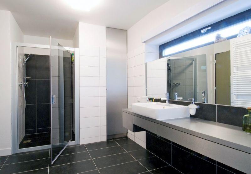 Kúpeľňa na prízemí ctí základnú farebnú škálu čiernej, šedej a bielej.