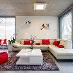 Priznaný železobetónový strop, veľkoformátová dlažba pripomínajúca betón a jednoduchý biely interiér s niekoľkými červenými akcentmi naznačujú triezvy a moderný vkus majiteľov domu.