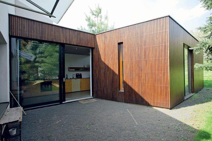 Prístavba má jednoduchú pravouhlú formu s plochou strechou a je postavená z tradičných materiálov – tehly v kombinácii s oceľobetónovými stropnými doskami a založením na betónovej doske. Drevený obklad fasády definitívne odlišuje prístavbu od pôvodného rodinného domu a navodzuje dojem záhradného domčeka.