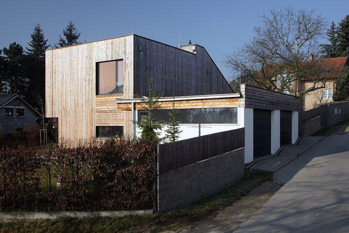 Zo severu, od ulice, na dom nadväzuje relatívne samostatný blok s garážou a krytým parkovacím státím. Rozdielnosť funkcií architekt zdôraznil aj odlišnou fasádou – drevo tu vystriedala svetlosivá omietka.