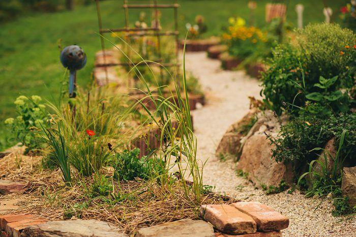 Suchý múrik zo starých škridiel, dreva, kameňa a tehál v nepravidelnom organickom tvare dodal záhrade neuveriteľné čaro.