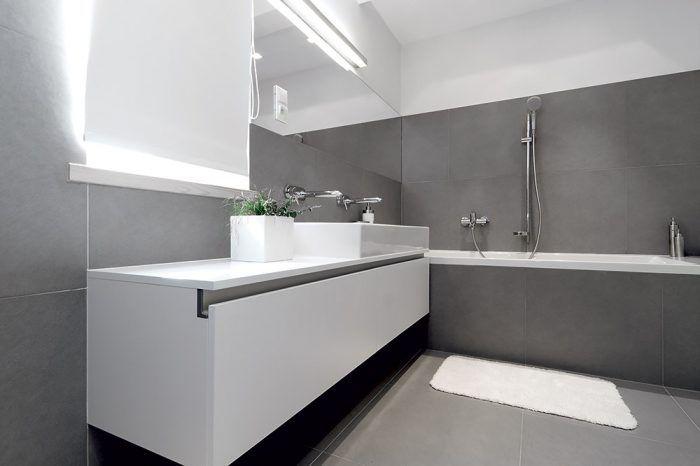 """Aj do kúpeľne na poschodí sa prenáša myšlienka praktického využitia priestoru. Šikovne je vyriešený odkladací priestor pod umývadlom – v podobe priestranných zásuviek. V kúpeľni je obklad len na nevyhnutnej ploche, aby pôsobila """"civilnejšie"""". Na neobkladaných častiach steny je biela štruktúrovaná tapeta odolná proti vode."""