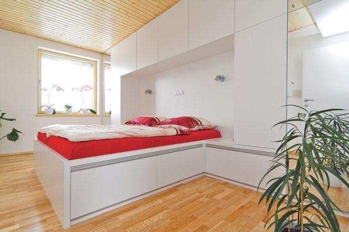 Aj spálňa je vyriešená čisto a prakticky. Drevená podlaha a strop sú doplnené bielym nábytkom s čistými líniami a s množstvom odkladacieho priestoru. Farby do interiéru vnáša pestré povlečenie a kvety. Nie je teda problém zmeniť jeho výraz.