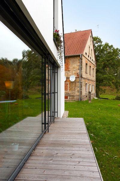 Domček je vďaka veľkoplošnému zaskleniu úzko spätý s prírodou.