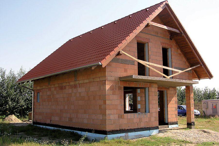 Stavba tehlového rodinného domu so sedlovou strechou.