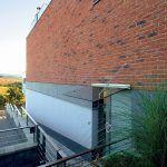 Použitie exteriérových stavebných materiálov je založené na vzájomnom farebnom a povrchovom kontraste. Pôsobivá je najmä kombinácia keramického obkladu so vzhľadom surovej tehly a antracitových obkladových fasádnych dosiek s omietanou časťou prízemia. Moderná a výrazovo čistá architektúra domu sa pritom prispôsobila svahovitosti pozemku a polohe prístupovej cesty.