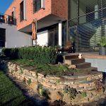 """Dom je citlivo osadený v teréne a napriek potrebným úpravám pozemku aj formou oporných múrov nepôsobí rušivo. """"Pozemok nám veľkosťou úplne vyhovuje, máme kúsok vlastnej zelene, ale nie sme otrokom záhrady,"""" zhodujú sa majitelia. O záhradu navrhnutú architektom sa celoročne stará domáca pani a záhradnícka firma napráva škody spôsobené zimou."""