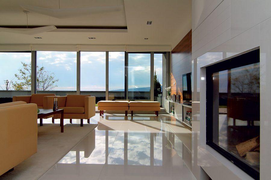 Odvahu si tu nikto nedokazoval farebnou, štrukturálnou alebo nábytkovou pestrosťou. Vzletný biely interiér pridržali pri zemi žule príbuzné obklady stien, kozuba a svetlá lesklá dlažba. Spojenie s exteriérom skoro dokonalé.