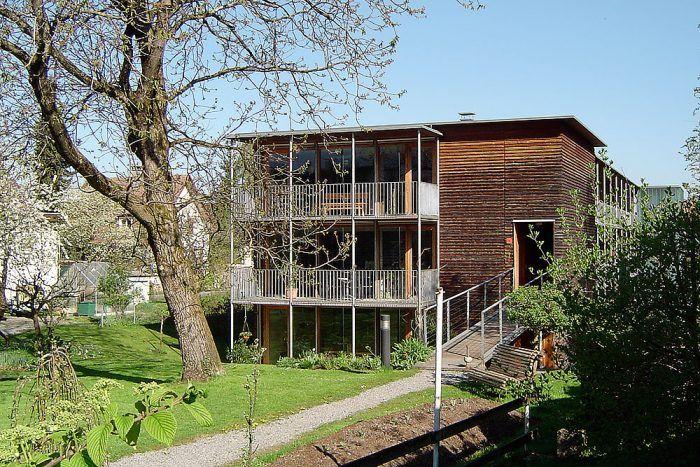 Trojpodlažný bytový dom v rakúskom Voralbergu je tiež postavený v pasívnom štandarde. Pre tento spôsob výstavby je typický kompaktný tvar s južne situovanými presklenými fasádami. Ďalším charakteristickým znakom je samostatne stojaca oceľová konštrukcia pavlačí na južnej a juhovýchodnej fasáde domu. Konštrukčné riešenie bráni vzniku tepelných mostov a pavlač má kumulovanú funkciu. Prepája interiér s exteriérom a zároveň je aj tieniacim prvkom veľkých zasklených plôch.