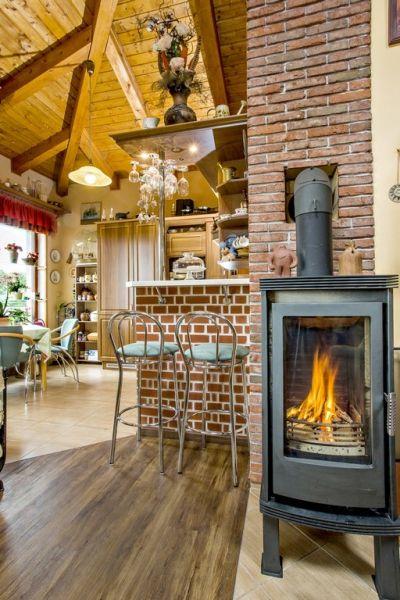 Kozubové kachle pomáhajú v zime s vykurovaním. Prechod z hlavnej obytnej miestnosti do kuchyne je naznačený premenou povrchu podlahy a obloženým kuchynským barom.