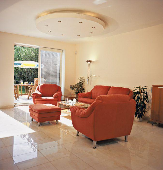 Interiér obývacej izby je ladený v teplých farebných tónoch – od jemnej béžovej a marhuľovej až po sýte červenkasté čerešňové drevo či výraznú terakotovú farbu sedačky.