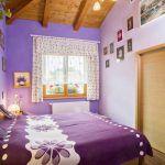 Levanduľový odtieň dodal spálni príjemnú pastelovú atmosféru a zvýraznil drevený strop.