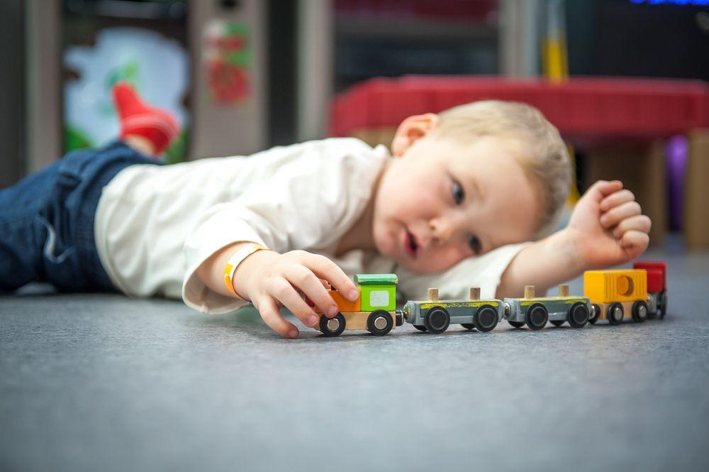 chlapec sa hrá s vláčikom na podlahe