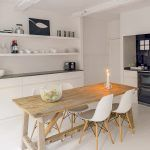 V kuchyni vytvárajú elegantný kontrast s bielymi stenami a jednoduchou bielou linkou lesklé čierne plochy obkladačiek, pracovných dosiek a spotrebičov s retro dizajnom.