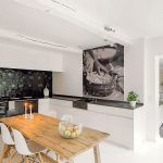 Kuchyňa je v priamom kontakte s obývačkou. Spája ich nielen priestor a kontakt so záhradou, ale aj biele steny a jednoduché vybavenie. Iba pôvodnú podlahu z drevených dosiek vystriedala v kuchyni nová biela dlažba.