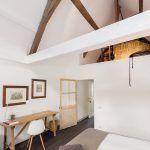 Aj v hosťovskej izbe v podkroví dotvára čistý bielo-drevený základ interiéru niekoľko kúskov nábytku so zaujímavým dizajnom.