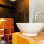 V zadnom trakte domu umiestnili atypickú kúpeľňu s dizajnovým umývadlom na drevenej nohe.