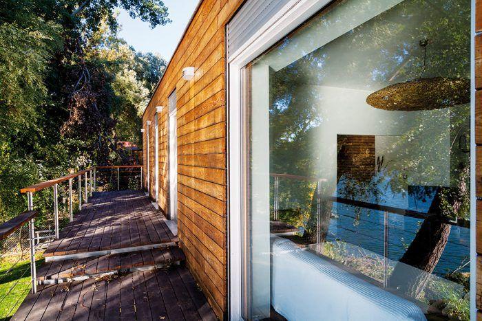 Sklenená stena opticky neruší: vonkajšie sedenie na celodrevenej terase sa takto prepojilo s priestorom obývačky, jedálne a kuchyne.