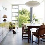 Moderný nábytok na mieru nekonkuruje prvkom z obdobia moderny. Kreslá s čalúnením z dielne Jo a dánske svietidlo nad kuchynským stolom v takomto rozložení o to viac vynikne.