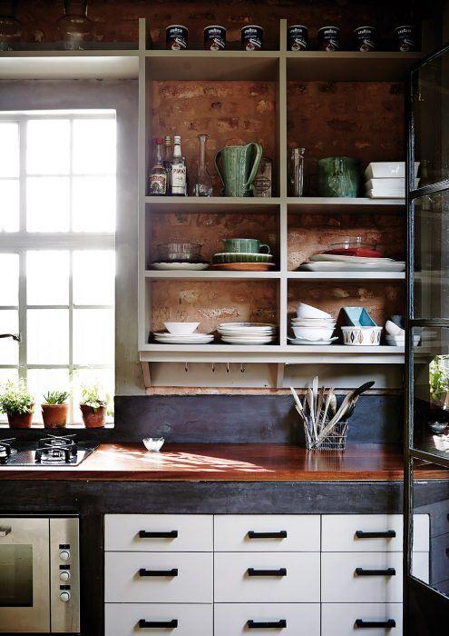 Hra s textúrami. Nezvyčajné lakované drevené úchytky zásuviek sú na dotyk jemné ako hodváb a zmierňujú dojem prísnej funkčnosti betónového kuchynského ostrova, rovnako ako odolná pracovná doska z afrického mahagónu, ktorá vďaka červenkastej farbe pôsobí teplo a prívetivo. Ďalšiu vrstvu textúry vnáša do kuchyne stena z neomietnutých tehál.