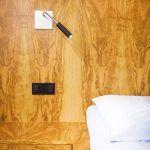 Minimalisticky poňaté nočné lampy sú zabudované priamo do drevenej zásteny.