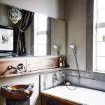 Zjemnený industriál. V kúpeľni pri rodičovskej spálni je rovnako ako v celom dome veľké kovové okno v štýle priemyselných budov orámované betónovou šambránou. Industriálne prvky sú aj tu zjemnené drevom – umývadlom z tíku, obložením vane a poličkou z orecha.