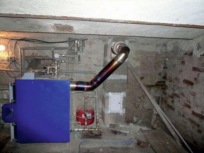 """Majiteľ si kúpil komínový systém a sám si ho vystaval. Niekto mu poradil, že aký je výstupný prierez na kotle, taký musí byť aj prierez komínového prieduchu. Okrem tohto omylu nebral do úvahy ani výšku komína a atmosférické tlaky. Dymovod napojil profesionálnymi dielmi napevno –bez akejkoľvek dilatácie do šamotového hrdla; vplyvom teploty sa tento materiál roztiahol tak, že odtrhlo šamotové zaústenie. Prípojka kotla má mať menší vnútorný prierez, 5-milimetrovú medzeru na dilatáciu, ktorú zabezpečí tesnenie """"azbestovou"""" šnúrou. Vplyvom nízkych teplôt v pivničnom priestore, polohy domu priamo pod horou a """"škrtenia"""" kotla na minimálne horenie (aby sa nemuselo často prikladať) teploty splodín dosahovali 40 až 60 °C, dochádzalo k vnútornému orosovaniu, rosa na seba postupne viazala častice dymu a tak sa vytváral decht – vlhká čierna usadenina. Keď však začal po mesiaci majiteľ naplno kúriť, decht sa vznietil a odtrhlo hrdlo šamotovej rúry."""