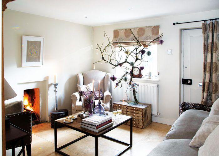 V obývacej izbe vo vianočnom období vyniká vyzdobená vetva jablone. Odtiene bielej, sivej a hnedej tu dopĺňa fialová, ktorá sa objavuje na jabloni aj na viacerých dekoráciách na konferenčnom stolíku.