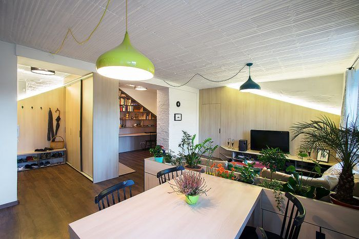 """Kvetinový črepník len v náznaku oddeľuje obývaciu izbu a kuchyňu. Je akýmsi medzičlánkom, vďaka ktorému sa majú sedačka a jedálenský stôl o čo """"oprieť""""."""