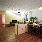 """Dvere skryté v drevenom obklade vedú do spálne. Svetlé drevo zvolili architekti ako medzistupeň medzi tmavou """"pánskou"""" podlahou a bielymi povrchmi stien a stropu. Zároveň však byt presvetľuje, keďže denné svetlo prúdi do priestoru len jednostranne."""