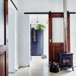 Luxus šatníka v inak pomerne malom dome umožňuje, aby spálňa nebola zaprataná haraburdím, ani z nej neukrojili skrine. Dvere s drôteným sklom sú odkazom na pôvodný štýl interiérov v tejto lokalite. Sú však posuvné, zavesené na oceľovej koľajničke. Sú tak novou interpretáciou tradície a zároveň praktickým moderným riešením, ktoré šetrí priestor.