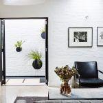 Z obývačky sa dostanete do záhrady cez betónové bloky umiestené vo vodnej nádrži. Sklenené dvere a striktne členený exteriér s geometrickými líniami posilňujú pocit súvislosti s interiérom.