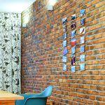 Vlastnoručne vyrobená dekorácia na tehlovej stene. Fotografie z ciest na oceľových lankách s ťažidlami na koncoch. Krásne jednoduchá a hravá inšpirácia od majiteľky.