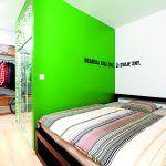 Spálňa sa nachádza za kúpeľňou a kuchynskou linkou, ktorej zadnú stranu tvorí šatník. Zelená olejová farba, ktorou je zvýraznený blok kúpeľne, pokračuje aj v spálni. Architekti sa potešili nápadu majiteľky – napísať svoje krédo na stenu.