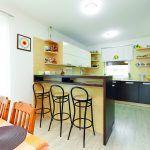 Kuchyňa a jedáleň Na severovýchodej strane je voľne spojená s obývačkou. Poruke sú zabudované kuchynské spotrebiče a vedľa nich chladná komora na potraviny.