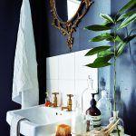Vizuálne stvárnený príbeh pokračuje v kúpeľni drevenou štetkou na holenie, sklenými nádobami a listami rastlín. Ozdobné starožitné zrkadlo pôsobí ako dramatický moment a zároveň závan blahobytu.