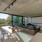 Dominantou veľkorysej obývacej izby bieleho domu je atypické, sčasti obojstranné sedenie. Minimalistické vybavenie a hladká cementová stierka na podlahe sú prispôsobené bývaniu s malými deťmi.