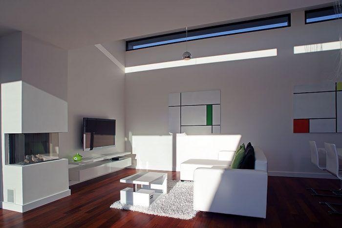 Minimalistický interiér otvoreného denného priestoru dokonale ladí s obrazmi na stenách. S bielymi stenami a nábytkom kontrastuje podlaha z dreva merbau, ktorá celý dom pocitovo prehriala.