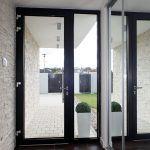Kamenný obklad jednej zo stien, ktorý prechádza cez vstupné dvere z fasády až do interiéru, je decentným oživením v minimalistickom duchu.