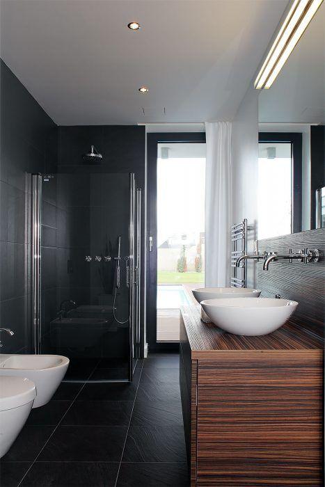 Pôsobivá kombinácia obkladu a dlažby vo farbe bridlice, elegantnej bielej keramiky a dreva wenge je zámerne rovnaká v oboch kúpeľniach v dome.