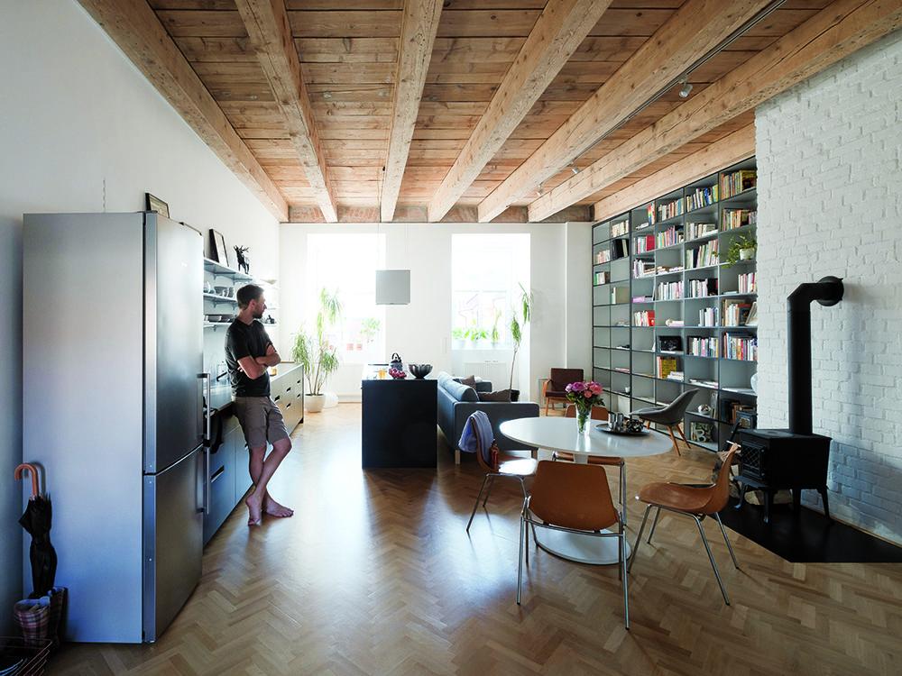 Otvorený denný priestor, očistený od nánosov, ktoré sem vniesli predchádzajúci majitelia, je centrom zrekonštruovaného bytu. Okrem veľkorysejšej podlažnej plochy získal pri prestavbe aj pôsobivú výšku a odkrytý pôvodný trámový strop. Ďalším zaujímavým prvkom je vstavaná knižnica, ktorá tvorí hranicu medzi dennou a nočnou zónou.