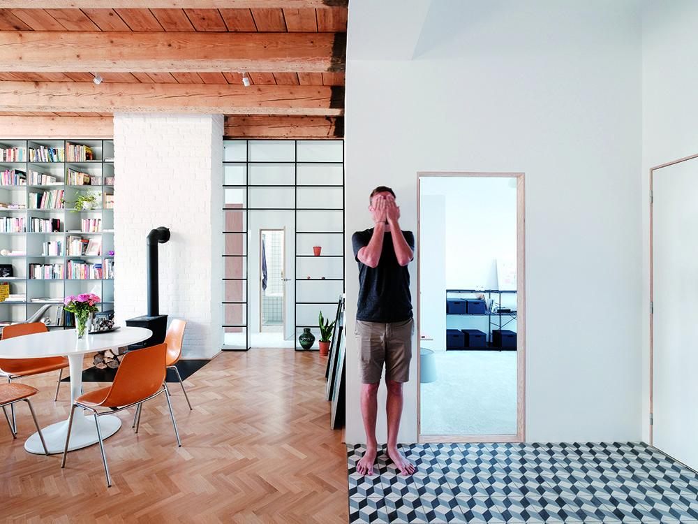 Staré s novým. Nabielo natreté tehlové steny a drevené trámy, k tomu nábytok s decentným dizajnom a hranice naznačené nábytkom a zmenou povrchov – kontrasty v pokojnej harmónii.
