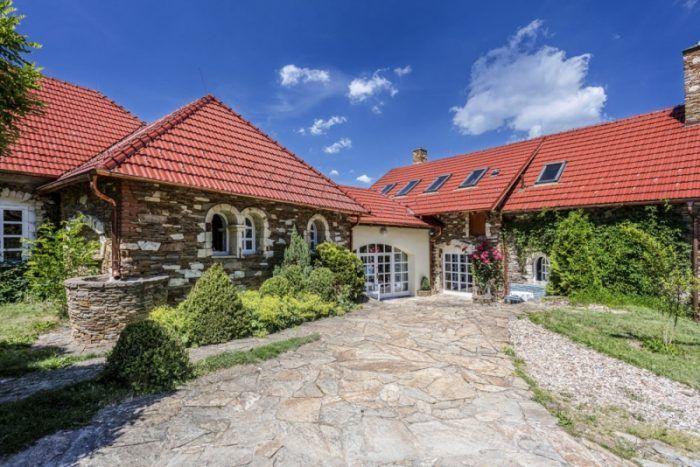 Pohľad na vstupnú časť domu. Rula a opuka, ktorými je obložený dom, pochádza z búračiek. Lomový kameň a oblúkové okná dodávajú stavbe jemne stredomorský nádych.